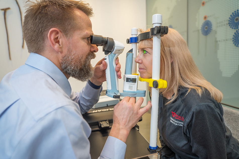 Global Outreach Division Co-Medical Director Jeff Pettey, MD, MBA, and Lori McCoy, outreach program manager, test the portable eye exam kit developed by a group of University of Utah mechanical engineering students.